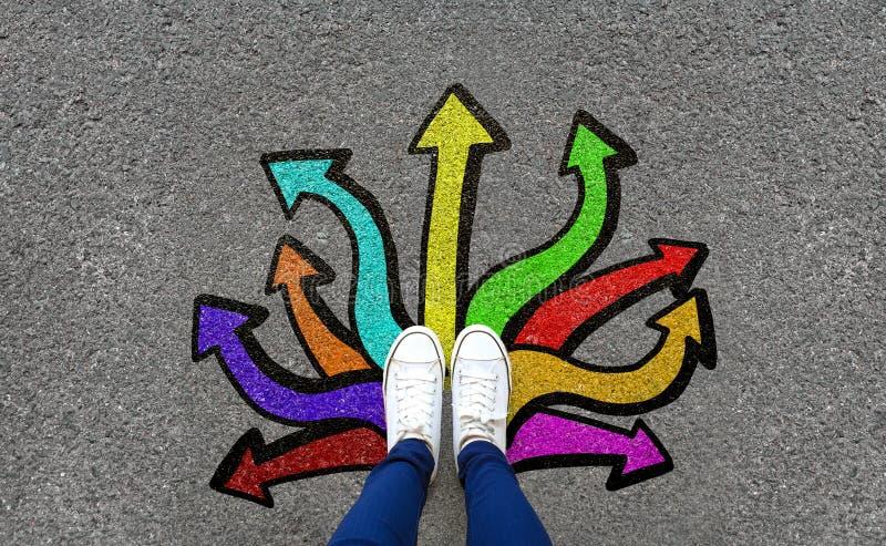 Ноги и стрелки на предпосылке дороги Пары положения ноги на дороге гудронированного шоссе с красочными выборами знака стрелки гра стоковые изображения