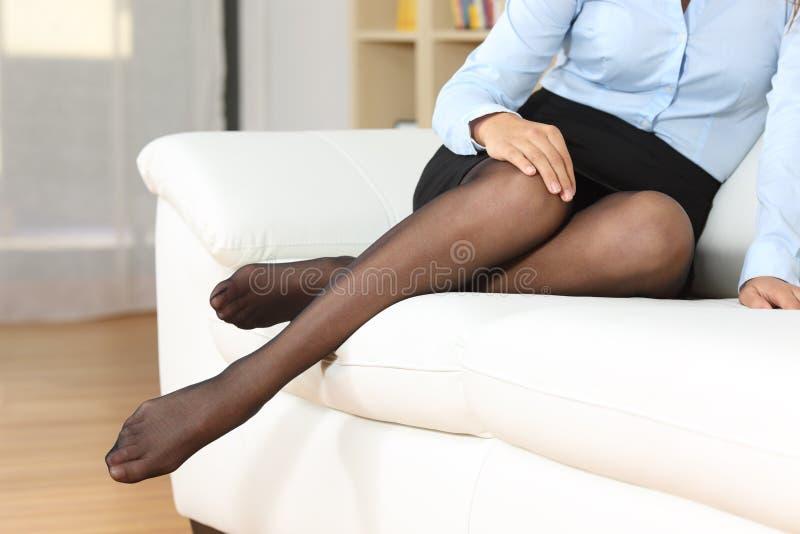 Ноги коммерсантки с нейлонами представляя на кресле стоковое фото