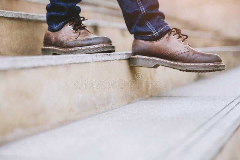 Ноги конца-вверх современного бизнесмена работая идя вниз с лестниц в современном городе стоковое фото