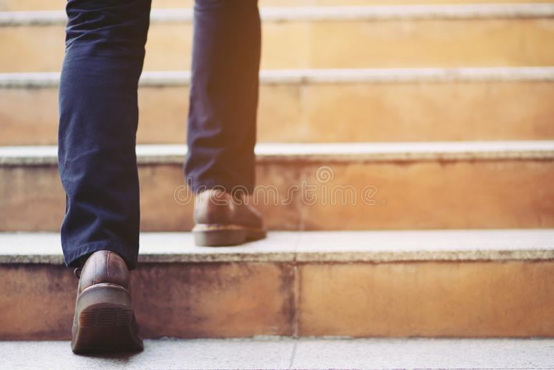 Ноги конца-вверх современного бизнесмена работая идя вверх по лестницам в современном городе в часе пик для работы в офисе спешно стоковые изображения rf
