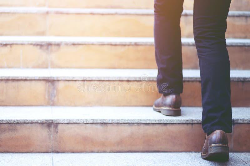 Ноги конца-вверх современного бизнесмена работая идя вверх по лестницам в современном городе в часе пик для работы в офисе спешно стоковая фотография