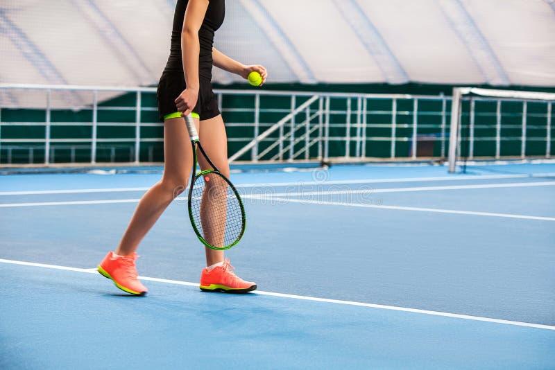 Ноги маленькой девочки в закрытом теннисном корте с шариком и ракеткой стоковая фотография rf