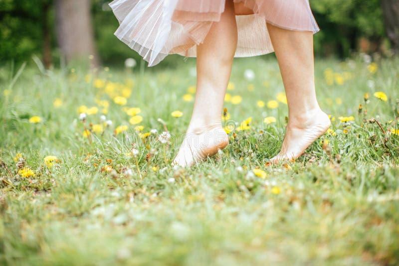 Ноги молодых босоногих женщин нося розовое платье стоя на одной ноге на зеленой траве с желтыми цветками, конце вверх стоковая фотография rf