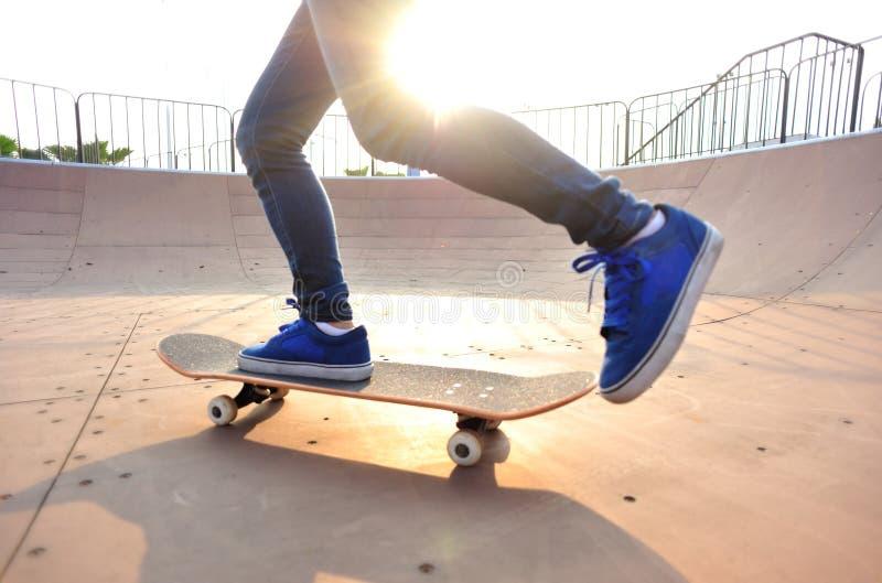 Ноги молодой женщины skateboarding на восходе солнца стоковое изображение rf