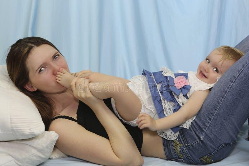 Ноги младенца молодой матери целуя детство счастливое стоковая фотография rf