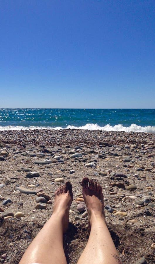 Ноги отдыхая в песке на пляже стоковая фотография