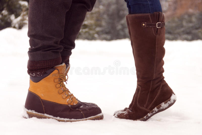 Ноги пар в влюбленности в парке в зиме стоковое фото