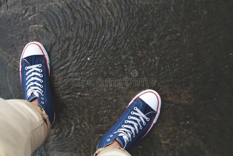 2 ноги при влажные ботинки стоя на лужице после дождя стоковое фото rf