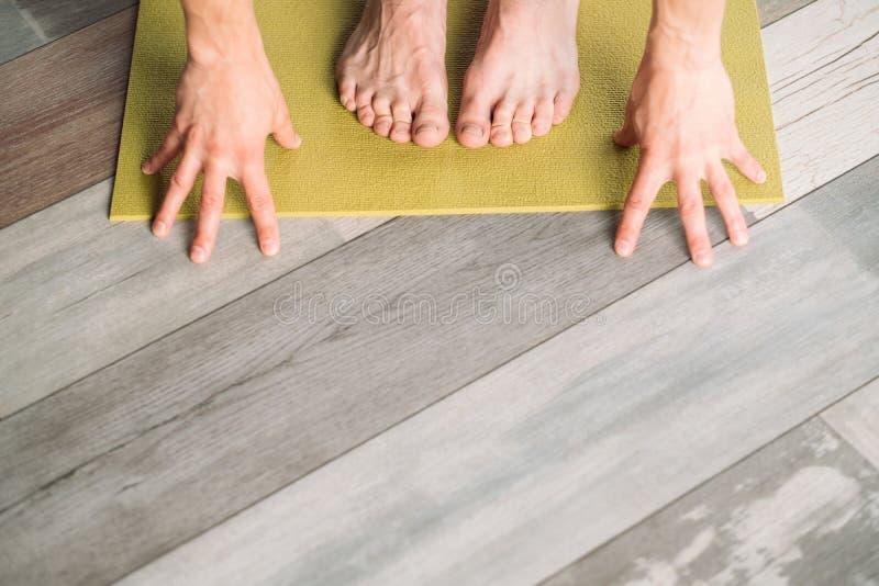 Ноги разминки фитнеса спорта йоги мужские вручают циновку йоги стоковые фотографии rf