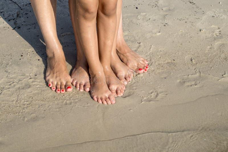 Ноги ребенка и мамы в песке моря стоковые изображения