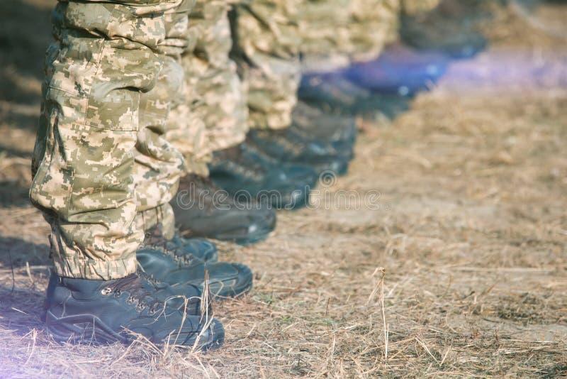 Ноги солдат в военной форме и ботинки стоя в линии на лагере стоковое фото
