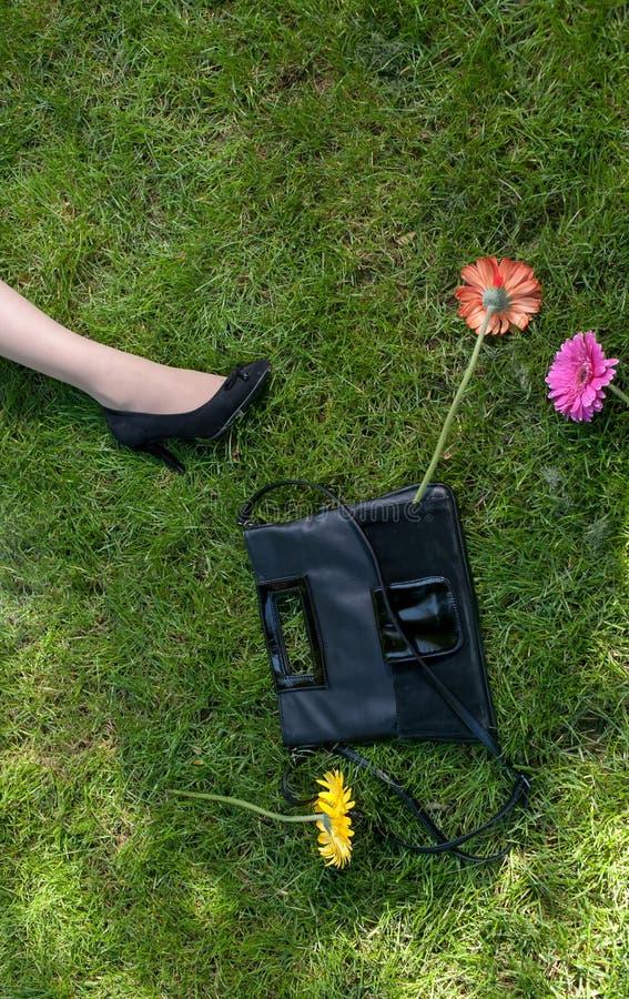 Ноги, сумка и цветки на траве стоковые изображения rf
