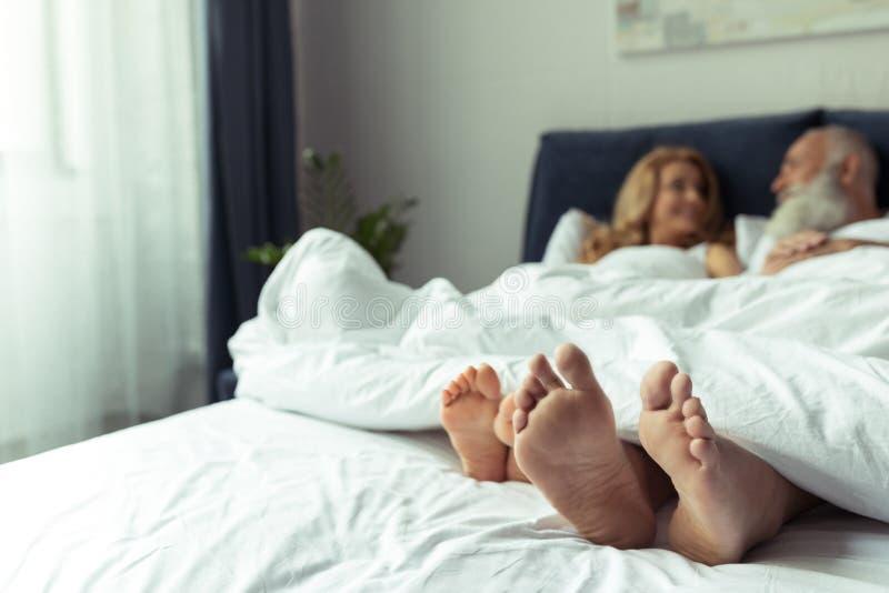 Ноги счастливых зрелых пар отдыхая совместно в кровати стоковое фото rf
