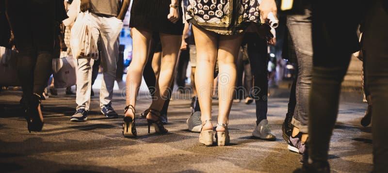 Ноги толпы низко снятые на crosswalk во время ночи стоковое фото rf