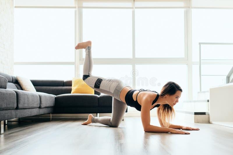 Ноги тренировки взрослой женщины и назад делать пинки осла планки стоковые изображения rf