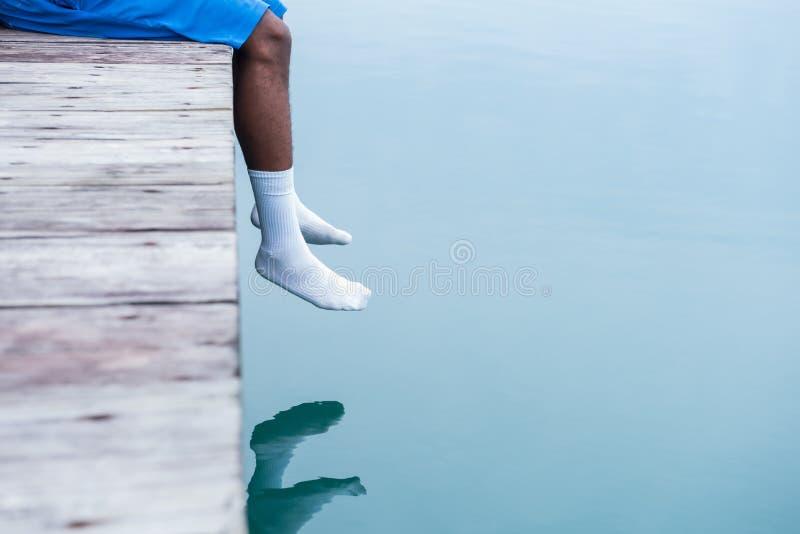 Ноги человека в белых носках вися над водой на доке стоковое фото