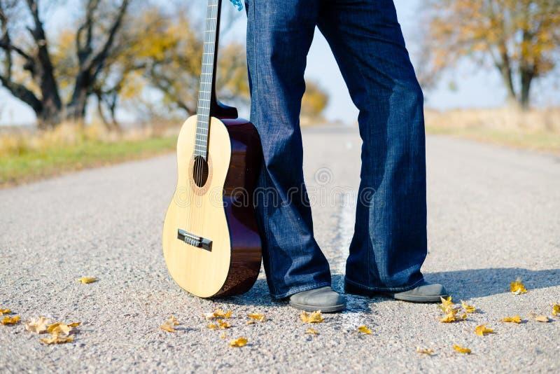 Ноги человека в джинсах с гитарой опорожняют проселочную дорогу стоковые фото
