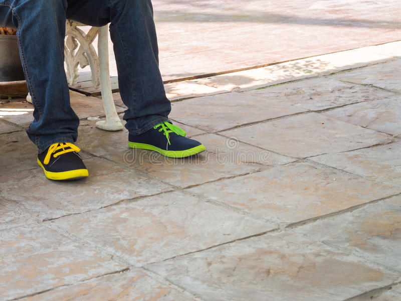 Ноги человека носят брюки голубых джинсов и snea цвета разницы стоковые фотографии rf