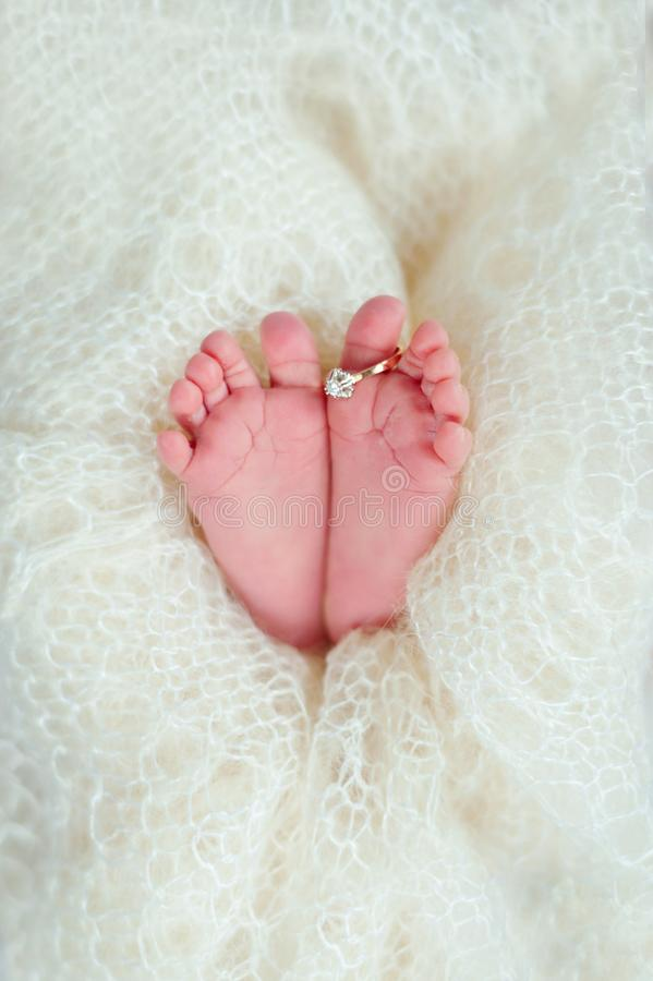 Ноги newborn младенца с обручальным кольцом мамы в теплом белом половике шерстей семья принципиальной схемы счастливая стоковые фотографии rf