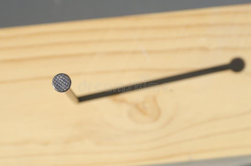 Ноготь в деревянной поверхности и тень напольная стоковое фото
