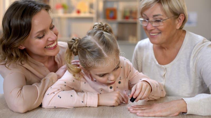 Ногти бабушки картины маленькой девочки делая маникюр, женскую красоту, отдых стоковое изображение rf