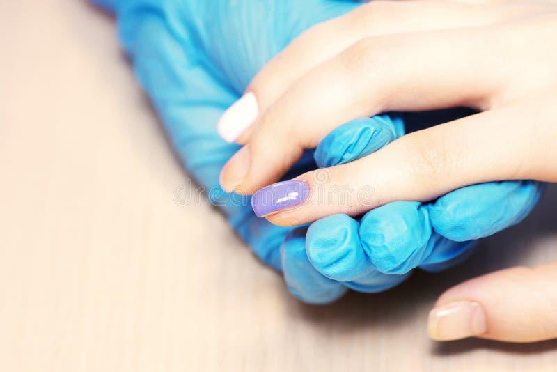 Ногти здоровой естественной женщины крупного плана в салоне красоты Ногти клиента картины руки Manicurist Покрывать ногти с гелем стоковая фотография