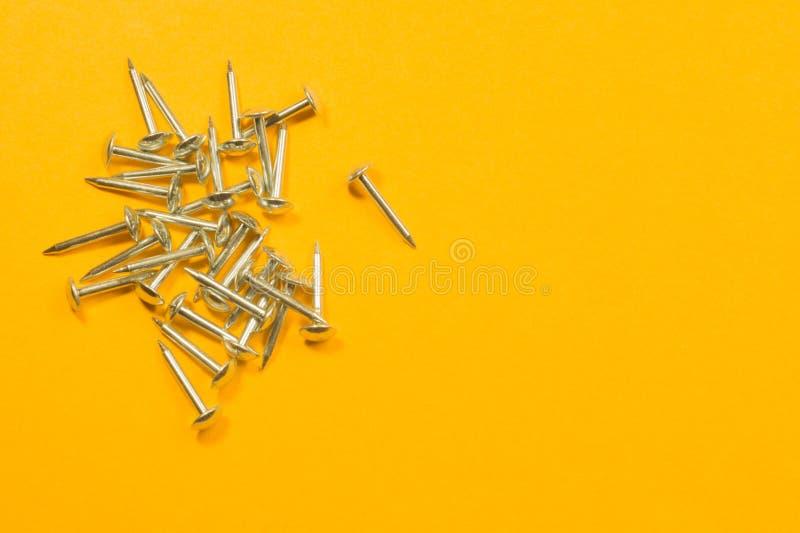 Ногти металла изолированные на желтой предпосылке инструменты деятельности стоковые изображения