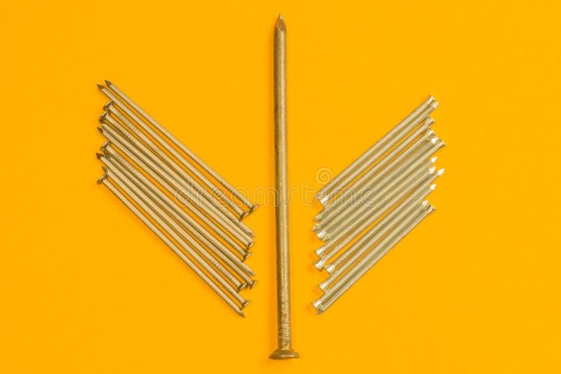 Ногти металла изолированные на желтой предпосылке инструменты деятельности стоковое фото rf