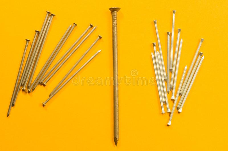 Ногти металла изолированные на желтой предпосылке инструменты деятельности стоковая фотография rf