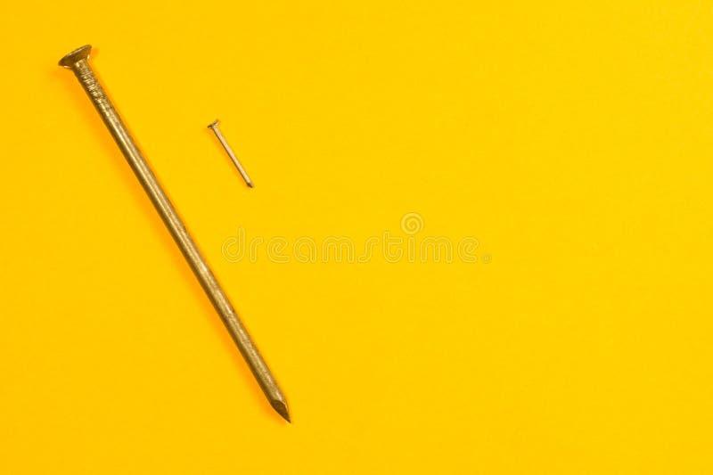 Ногти металла изолированные на желтой предпосылке инструменты деятельности стоковое изображение