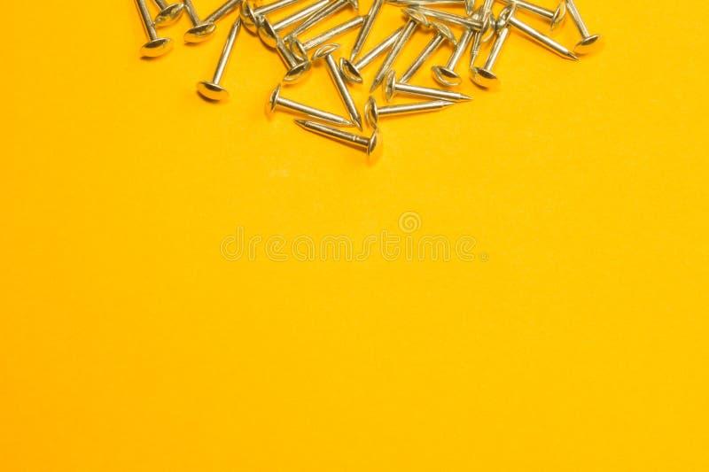 Ногти металла изолированные на желтой предпосылке инструменты деятельности стоковые фотографии rf