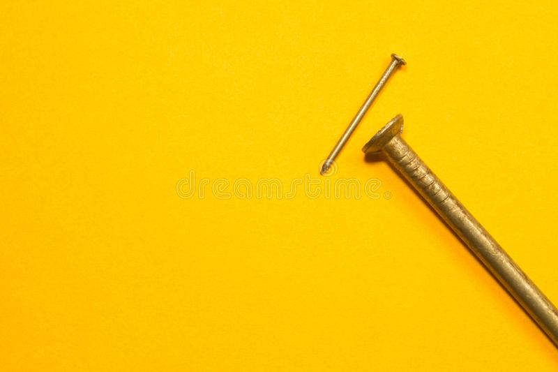 Ногти металла изолированные на желтой предпосылке инструменты деятельности стоковое фото