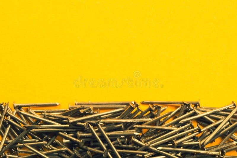 Ногти металла изолированные на желтой предпосылке инструменты деятельности стоковое изображение rf