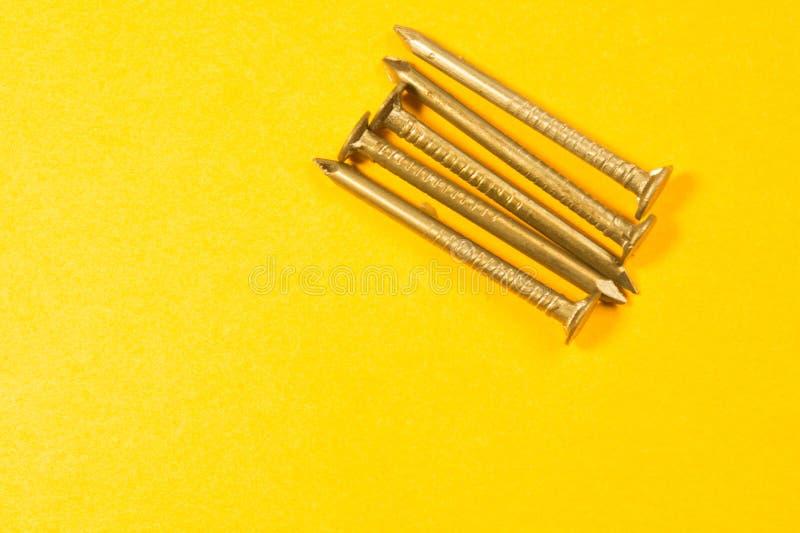 Ногти металла изолированные на желтой предпосылке инструменты деятельности стоковая фотография