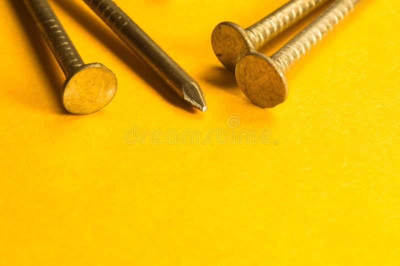 Ногти металла изолированные на желтой предпосылке инструменты деятельности стоковые изображения rf