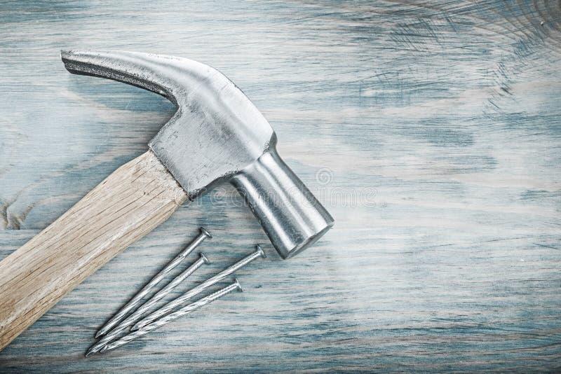 Ногти металла молотка с раздвоенным хвостом на концепции конструкции деревянной доски стоковые фотографии rf