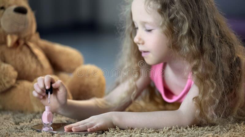 Ногти нежной маленькой девочки крася с блеском, ребенк мечтая для того чтобы вырасти вверх скоро стоковые изображения
