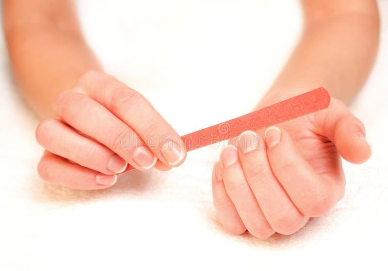 Ногти опиловки женщины стоковые фотографии rf