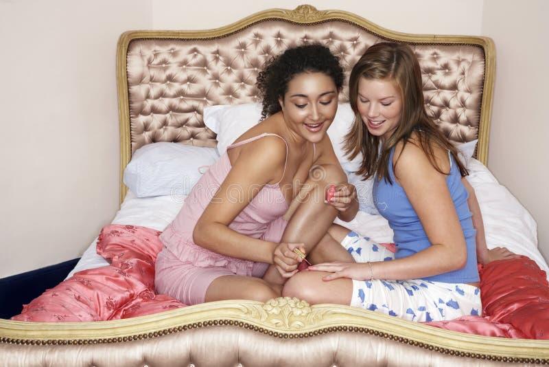 Ногти друга картины девочка-подростка на кровати стоковое изображение rf