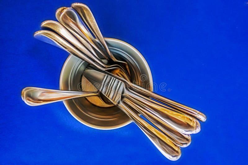 Ножи, ложки и вилки взгляда сверху в баке металла на голубой предпосылке стоковое изображение rf