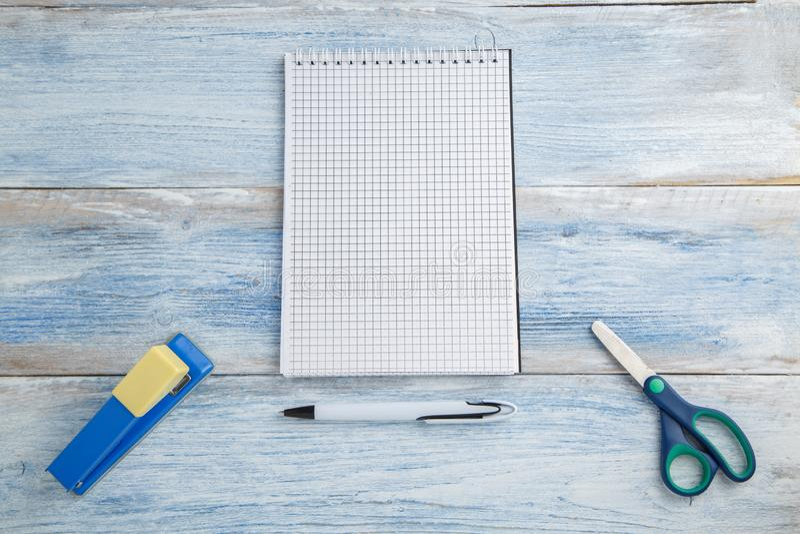 Ножницы, сшиватель и тетрадь с ручкой на голубой и белой затрапезной винтажной деревянной предпосылке r r стоковые изображения rf