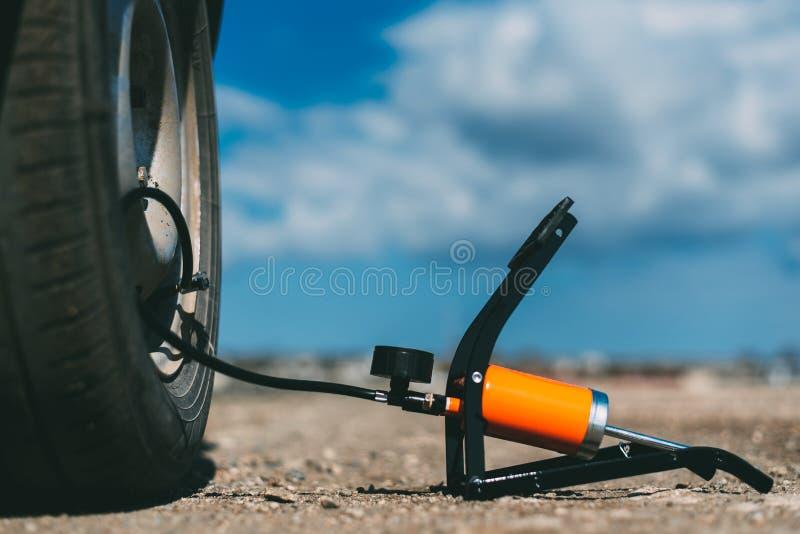 Ножной насос на поле рядом с автомобилем и колесом стоковые фотографии rf