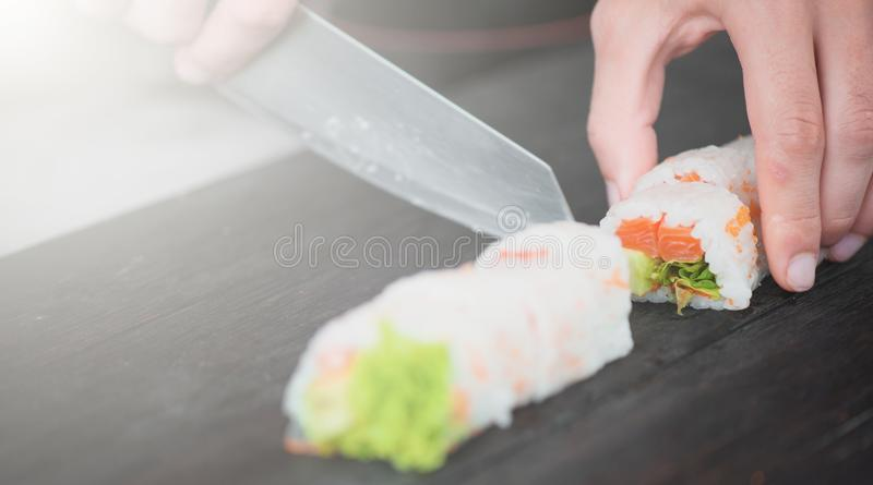 Нож в руке режет крупный план крена на деревянной доске стоковые фото
