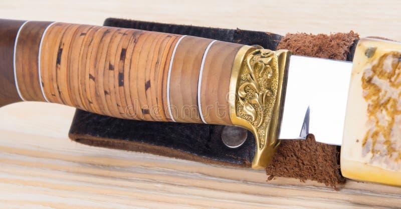 Нож для охотиться в случае, на светлой деревянной предпосылке стоковые изображения rf
