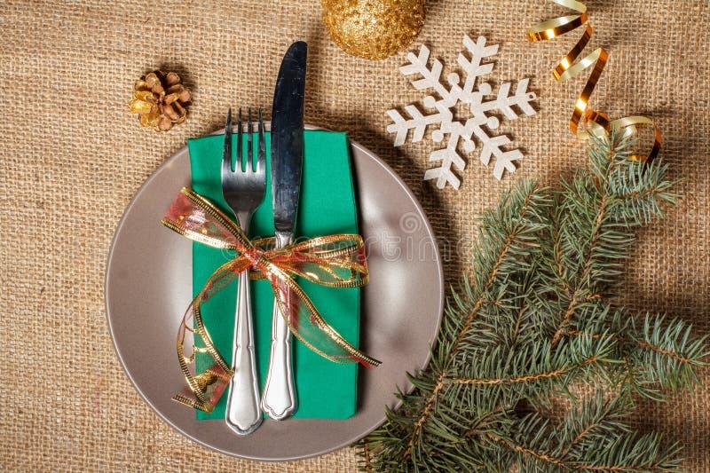 Нож и вилка на зеленых салфетке и плите, декоративная снежинка, стоковое изображение