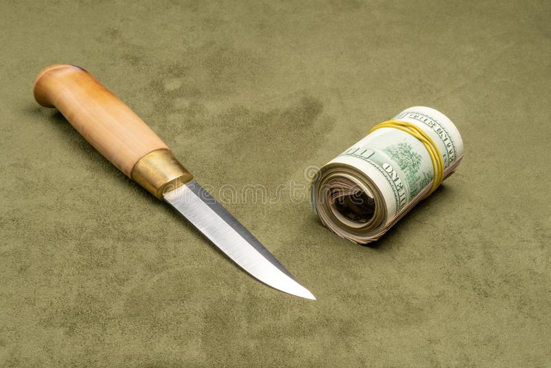 Нож и переплетенные доллары на зеленой предпосылке стоковые фотографии rf