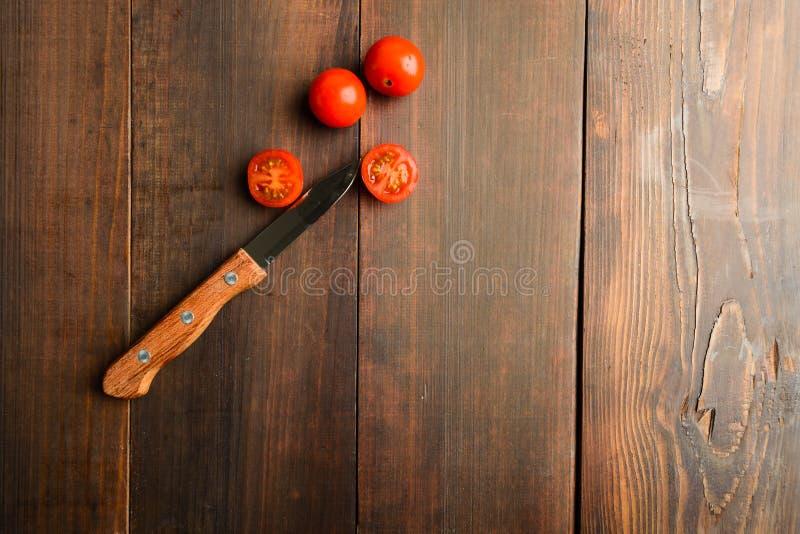 Нож с томатом вишни вырезывания и 2 всеми томатами стоковое изображение rf
