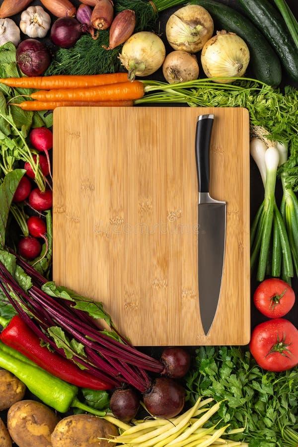 Нож шеф-повара на деревянной разделочной доске с предпосылкой свежих овощей : стоковая фотография rf