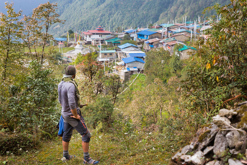 Нож keffiyeh бандита человека ратника нося над домами в деревне леса горы стоковое изображение