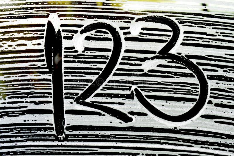 номера на картинах пены мойки на окне автомобиля стоковые изображения